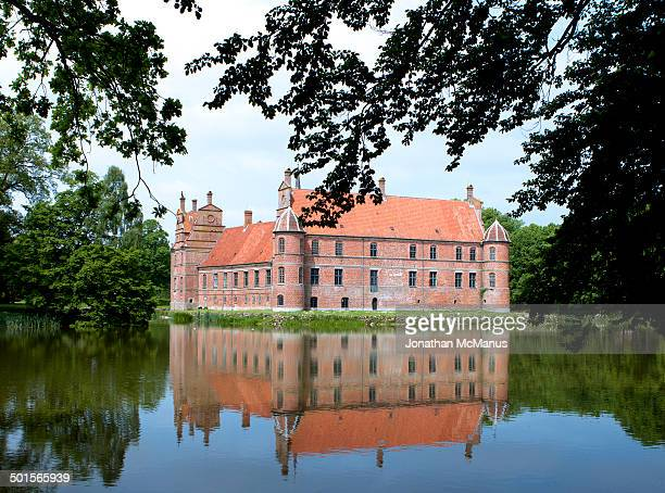 CONTENT] Rosenholm castle reflected in lake and framed by trees