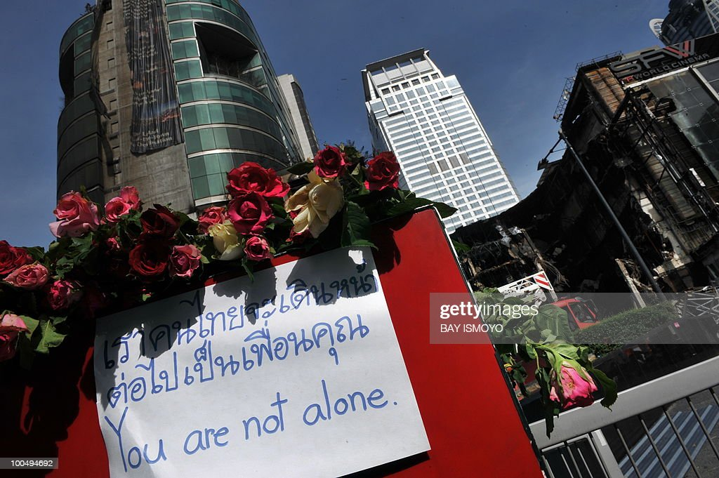 Roses and a sign stand in front of a collapsed Central World shopping mall in downtown Bangkok on May 25, 2010 following recent anti-government protests. Thai authorities will ask the government to extend a curfew in Bangkok and 23 provinces for another week in the wake of a crackdown on anti-government protesters, an army official said. AFP PHOTO / Bay ISMOYO