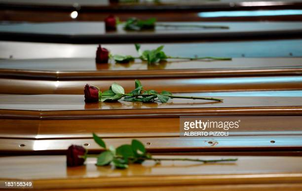 Roses are displayed on coffins of victims in an hangar of Lampedusa airport on October 5 2013 after a boat with migrants sank killing more than...