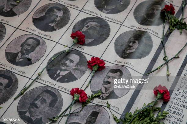 Roses are seen on the portraits of victims during a memorial to commemorate the 1915 Armenian mass killings on April 24 2018 in Istanbul Turkey...