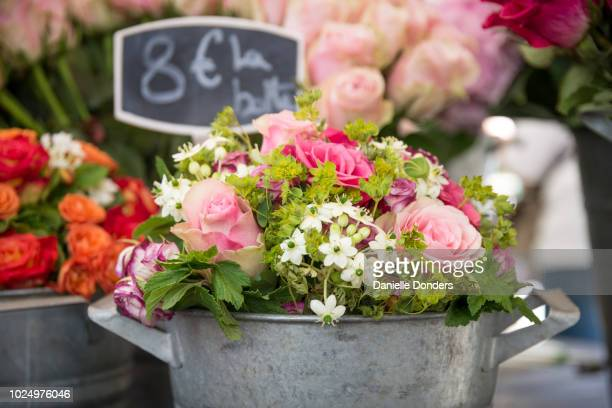 Roses for sale at a flower market, arranged in a metal bucket