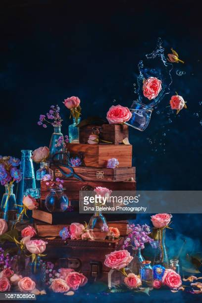 Roses in a falling vase with a water splash on a stack of books and boxes. Unbalance concept on a dark background