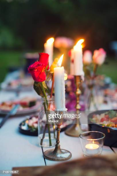 Roses in vase and lit candles amidst food on table at garden party