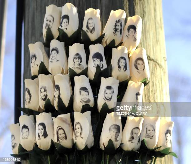 Roses with the faces of the Sandy Hook Elementry students and adults killed are seen on a pole in Newtown Connecticut on January 3 2013 Students at...