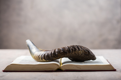 Rosh Hashanah (Hashana) (jewish New Year holiday) concept with Ram shofar (horn) with religious holy prayer book on table 1253102647