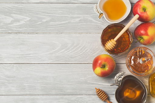 Rosh hashanah jewish new year holiday celebration concept. Honey and apples over wooden background. Top view 824907576