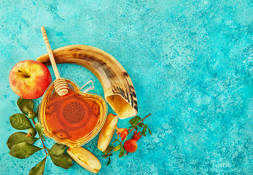 Rosh hashanah - jewish New Year holiday concept. A bowl in the shape of an apple with honey, pomegranate, shofar are traditional symbols of the holiday 1264612010