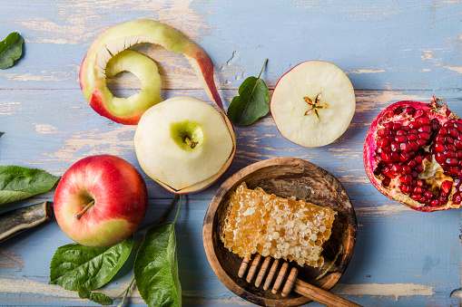 Rosh hashanah  (Hashana) - jewish New Year holiday concept. Traditional symbols: Honey jar and fresh apples with pomegranate and shofar - horn on a blue background. Copy space for text. View from above 1255204414