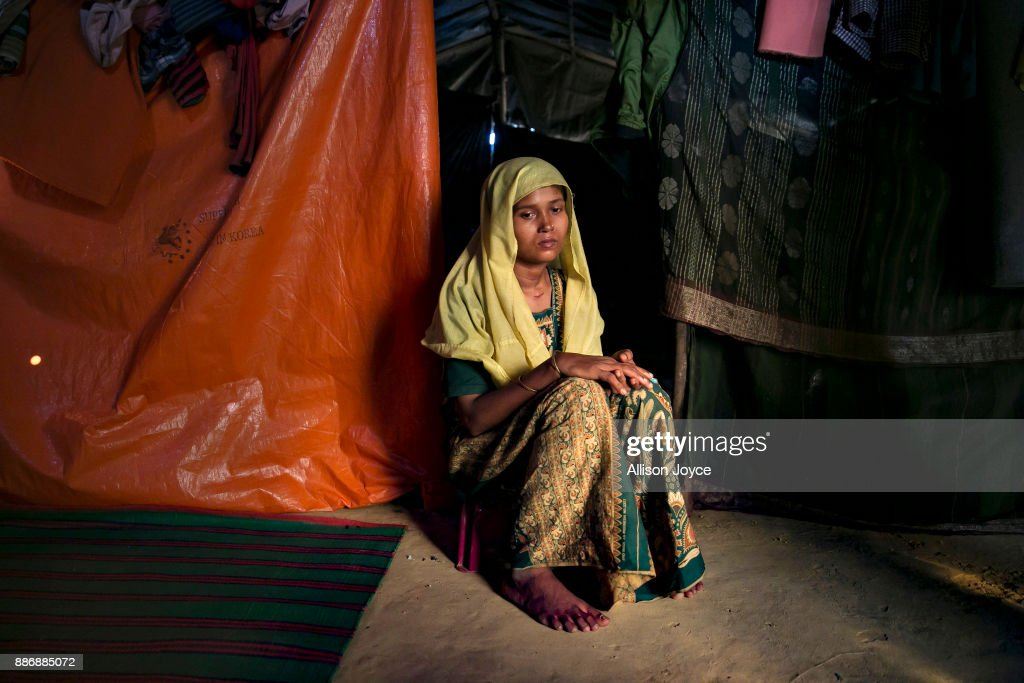 COX'S BAZAR, BANGLADESH - DECEMBER 01: Roshida Begum, 22, poses for a photo on December 1, 2017 in Cox's Bazar, Bangladesh. She fled to Bangladesh shortly after the August 25th attack from Tula Toli village in Myanmar. One day the military came to her village and threw petrol bombs and set houses on fire. They randomly shot anyone they say. She fled and hid on a riverbank, where the military found her and other people. Her husband swam across and escaped. They shot the young boys and stole the jewelry the women had. They took little children and babies and threw them into the river. Then they took us to a pond and made us kneel up to our necks in the water. A helicopter was circling overhead again and again. she says. The military took groups of 4-5 women into houses and raped them. My baby was 25 days old, they grabbed him from my arms and smashed him on the ground so hard, he died. The military took me and 5 other women into a house and raped us. After they were done, they slit our necks with machetes. They thought I was dead and they left and set the house on fire. I was the only one who escaped.' She says. She hid in a paddy field and in a forest until she came across another woman and her daughter, and together they crossed into Bangladesh. For 8 days they walked, surviving by drinking water from the paddy fields. They took a boat into Bangladesh and she went to the MSF clinic, where she spent 18 days recovering. Her husband found her there, and when she was discharged they moved into a camp. In the attack, she lost her mother, father, brother, all together she lost 17 members of her family. 'In Bangladesh, sometimes I'm happy, but then I'll see an old man and miss my father, or I'll see a woman with a baby, and I'll miss my son. I can't help but cry. I want justice from the world, why did they kill my mother and father and sisters? I hope the world will give me justice. They killed my parents and relatives for no reason.