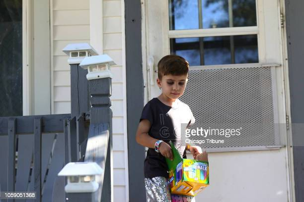Rosie Lohman carries a box of chalk outside her home Sept 15 in Milwaukee Rosie who has congenital adrenal hyperplasia is one of a growing number of...