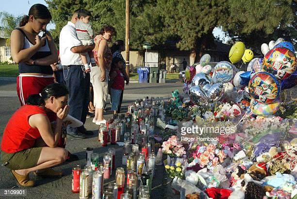 Rosie Millan wipes tears from her eyes while she and her 12yearold daughter Autumn look at a memorial in front of the home of Marcus Wesson on March...