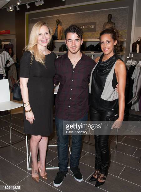Rosie Pope Kevin Jonas and Danielle Jonas pose for a photo at the grand opening of Destination Maternity Paramus on September 7 2013 in Paramus New...