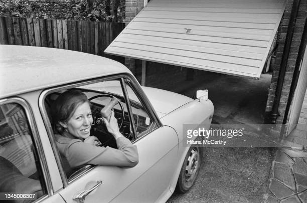 Rosilynd Laskin sits at the wheel of her car as she uses a handheld remote control to raise the door of her garage, location unspecified, 1973.