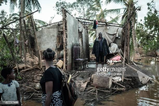 Rosita Moises Zacarias and her sister Joaninha Manuel look at their father Francisco Simon in their house destroyed by the cyclone Idai as they go to...