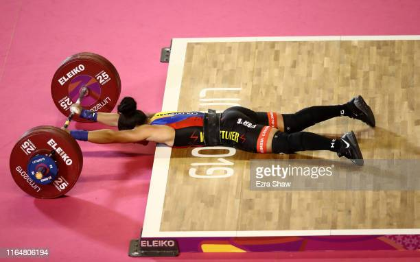 Rosive Silgado Atencio of Columbia lies on the ground after being unable to complete a lift during the women's weightlifting 59kg competition on Day...