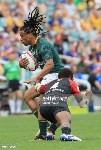 Rosko Specman of South Africa is tackled in the game against Papua New Guinea during the Sydney World Rugby Sevens Series tournament in Sydney on...