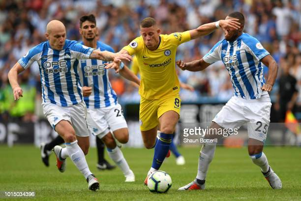 Ross Barkley of Chelsea is challenged by Aaron Mooy of Huddersfield Town and Mathias Zanka Jorgensen of Huddersfield Town during the Premier League...