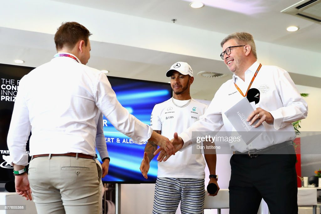 Ross Brawn, Managing Director (Sporting) of the Formula One Group and Lewis Hamilton of Great Britain and Mercedes GP congratulate the winners Benjamin Lambert and Alexander Gibson during the F1 Connectivity Innovation prize giving at Yas Marina Circuit on November 23, 2017 in Abu Dhabi, United Arab Emirates.