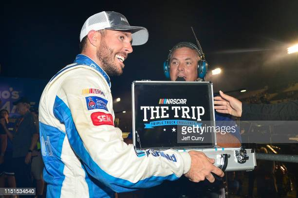Ross Chastain driver of the CarSheildcom Chevrolet celebrates as he receives his The Trip Triple Truck Challenge briefcase in victory lane after...