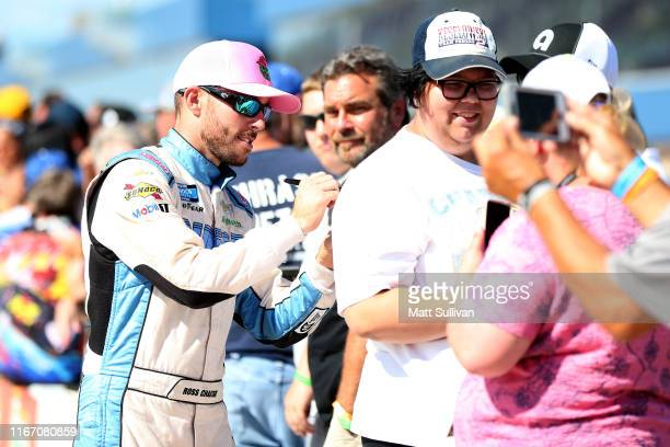 Ross Chastain driver of the Chevrolet signs autographs during qualifying for the Monster Energy NASCAR Cup Series Consumers Energy 400 at Michigan...