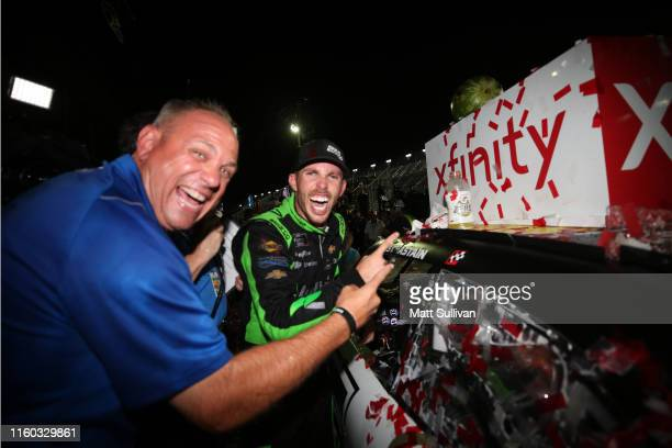 Ross Chastain driver of the Ellsworth Advisors Chevrolet applies the winner's sticker with Kauling Racing's Chris Rice in Victory Lane after the...