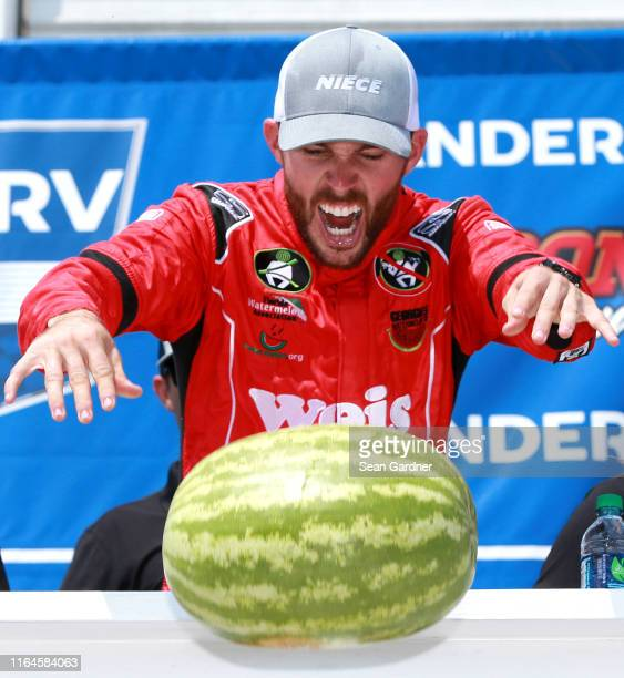 Ross Chastain driver of the Niece/Acurlite Chevrolet celebrates by smashing a watermelon in Victory Lane after winning the NASCAR Gander Outdoors...
