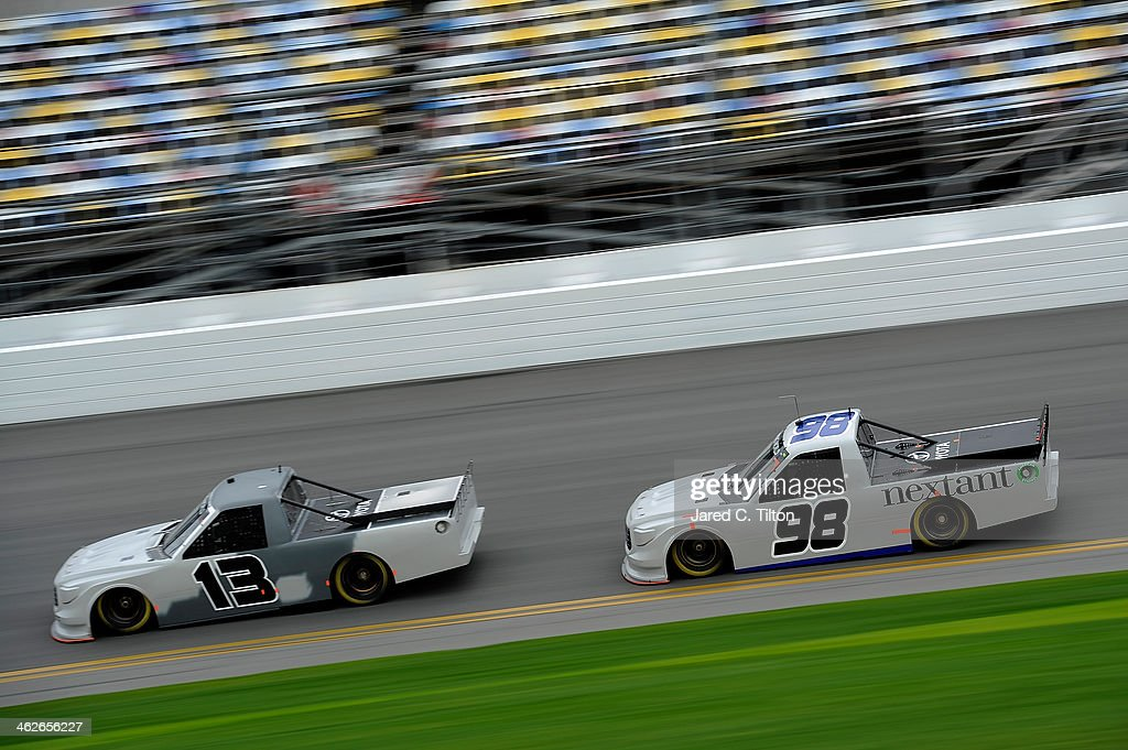 Ross Chastain, driver of the #13 Thorsport Toyota, leads Johnny Sauter, driver of the #98 Thorsport Toyota, during NASCAR Preseason Thunder at Daytona International Speedway on January 14, 2014 in Daytona Beach, Florida.