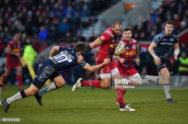 Ross Chisholm of Harlequins runs through a tackle by AJ MacGinty of Sale Sharks to score a try during the Aviva Premiership match between Sale Sharks...