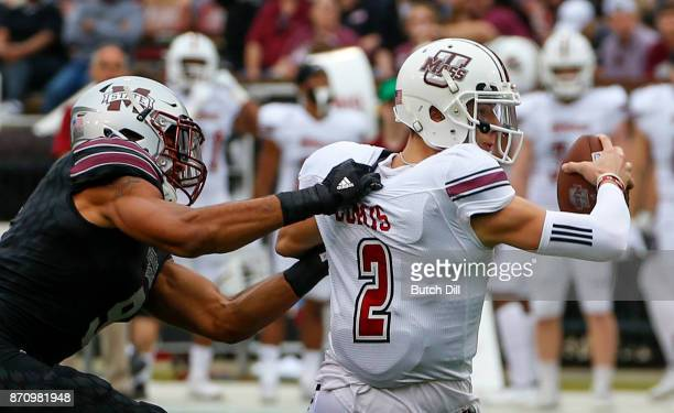 Ross Comis of the Massachusetts Minutemen is sacked by Montez Sweat of the Mississippi State Bulldogs during the first half of an NCAA football game...
