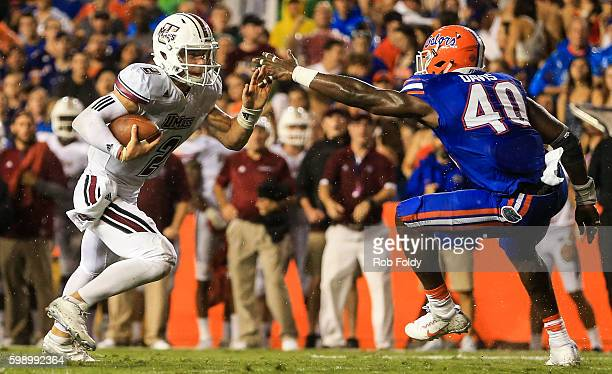 Ross Comis of the Massachusetts Minutemen passes Jarrad Davis of the Florida Gators to score a touchdown during the first half of the game at Ben...