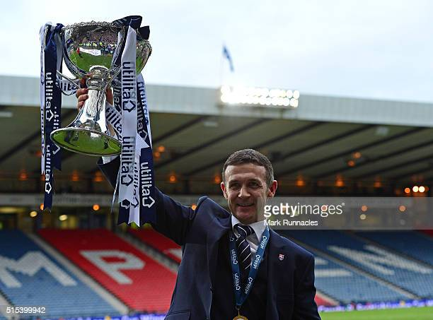 Ross County manager Jim McIntyre lifts the League Cup Trophy after his side beat Hibernian 2-1 during the Scottish League Cup Final between Hibernian...