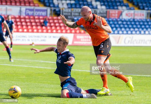 Ross County's Harry Paton goes down under the challenge of Mark Connolly and is booked for diving during the Scottish Premiership match between Ross...