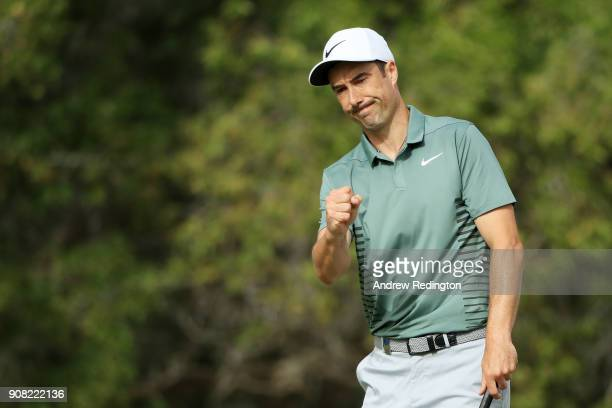 Ross Fisher of England reacts after holing a putt for bogie on the tenth green during the final round of the Abu Dhabi HSBC Golf Championship at Abu...
