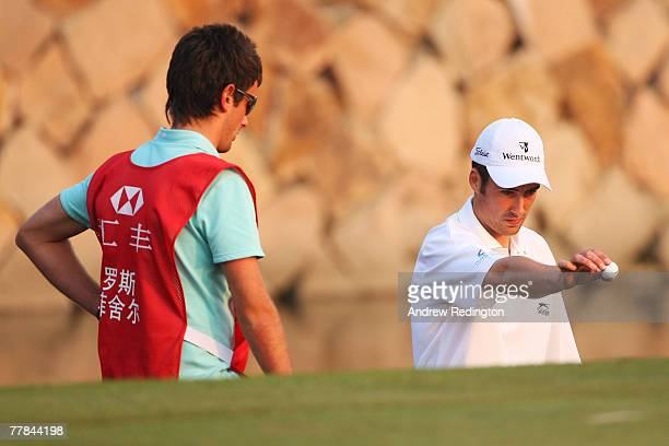 Ross Fisher of England takes a drop on the 18th green during the final day of the HSBC Champions at the Sheshan Golf Club on November 11, 2007 in...