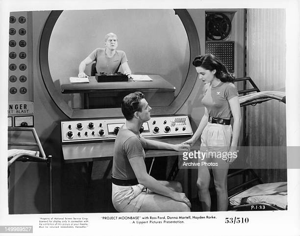 Ross Ford sitting before Donna Martell in control room in a scene from the film 'Project Moon Base' 1953