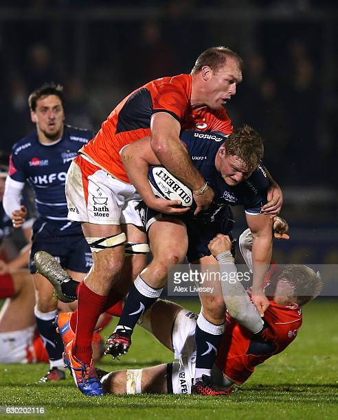 Ross Harrison of Sale Sharks is tackled by Schalk Burger of Saracens during the European Rugby Champions Cup match between Sale Sharks and Saracens...