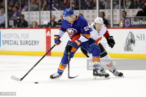 Ross Johnston of the New York Islanders fights for the puck against Mark Jankowski of the Calgary Flames in the second period during their game at...