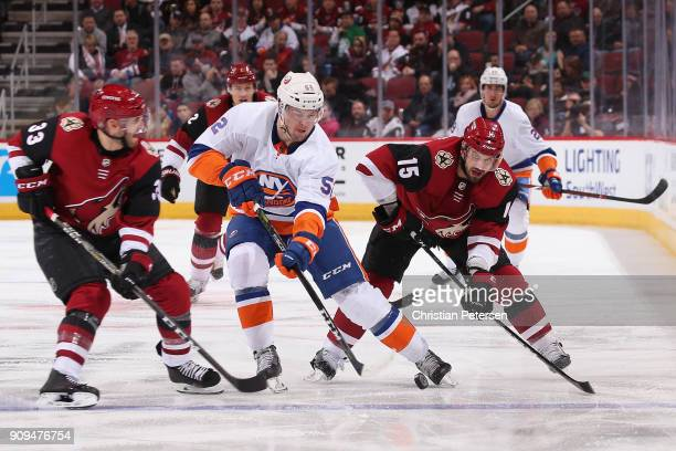 Ross Johnston of the New York Islanders skates with the puck between Alex Goligoski and Brad Richardson of the Arizona Coyotes during the NHL game at...