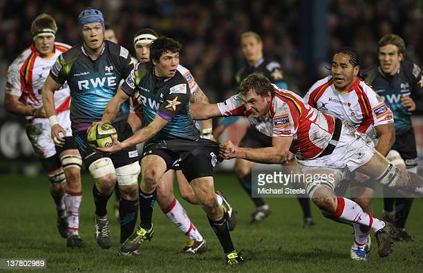 Ross Jones of Ospreys offloads a pass as Royce Cadman of Newport Gwent Dragons holds on during the LV Cup match between Ospreys and Newport Gwent...