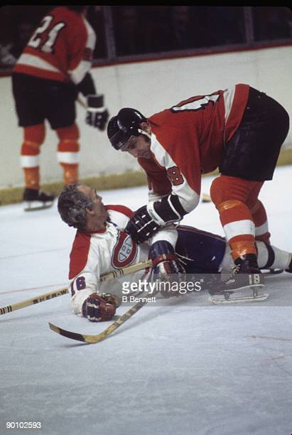 Ross Lonsberry of the Philadelphia Flyers battles Henri Richard of the Montreal Canadiens during a circa 1970's game at the Forum in Montreal Quebec...