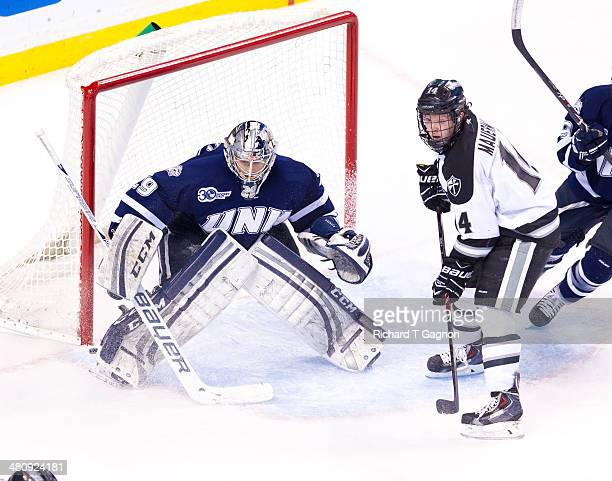 Ross Mauermann of the Providence College Friars battles against Casey DeSmith and Matt Willows both of the New Hampshire Wildcats during NCAA hockey...