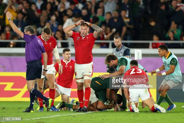 Ross Moriarty of Wales reacts as Damian de Allende of South Africa celebrates with teammates after scoring his team's first try during the Rugby...