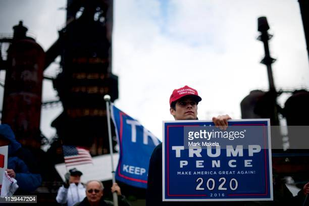 Ross Saveri clutches a TRUMP PENCE 2020 placard while joining fellow Donald Trump supporters demonstrating outside of a FOX News Town Hall with...