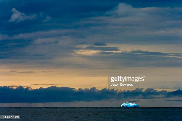 An iridescent blue iceberg floating across the sunset horizon in Antarctica.