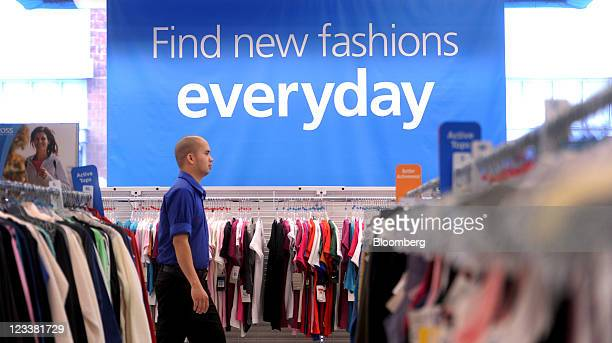 Ross Stores Inc. Sales associate walks past clothing displayed for sale at a location in San Francisco, California, U.S., on Wednesday, Aug. 31,...