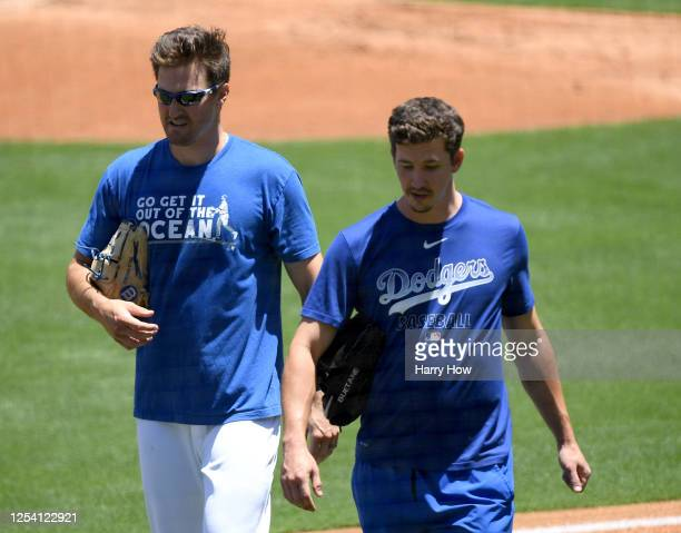 Ross Stripling and Walker Buehler of the Los Angeles Dodgers walk off the field at a summer workout in preparation for a shortened MLB season during...