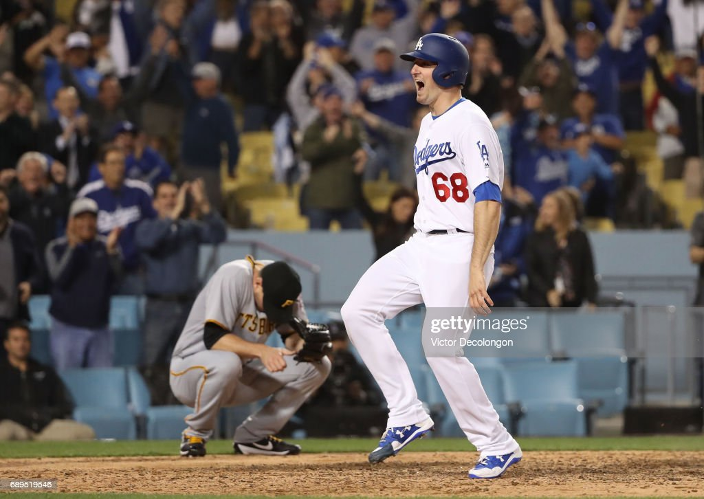 Ross Stripling #68 of the Los Angeles Dodgers reacts after scoring the game-winning run in the tenth inning as pitcher Daniel Hudson #41 of the Pittsburgh Pirates hangs his head after the MLB game at Dodger Stadium on May 9, 2017 in Los Angeles, California. The Dodgers defeated the Pirates 4-3 in the tenth inning.