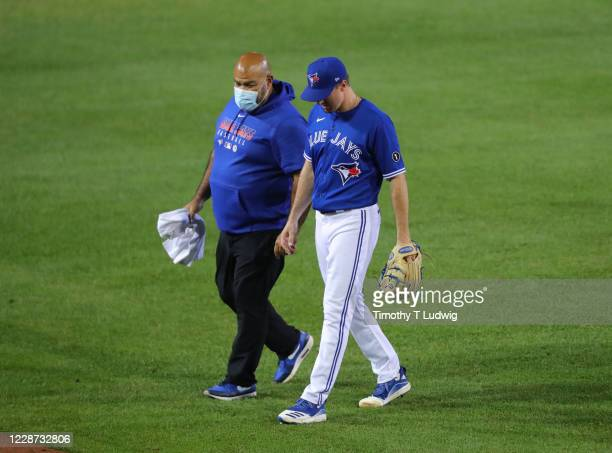 Ross Stripling of the Toronto Blue Jays leaves the game with a trainer after getting hit by a ball during the eighth inning against the Baltimore...