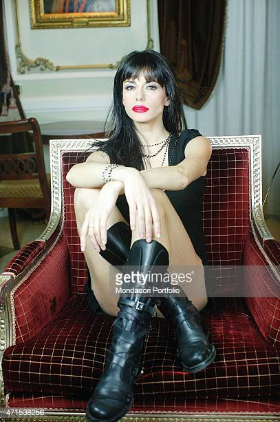 'Rossella Brescia Italian tv character dancer and anchorwoman posing for a photo shoot seated with her legs crossed on a red sofa Italy 2008 '