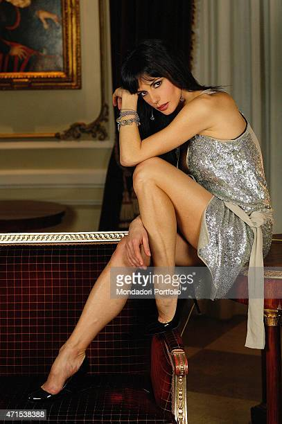 Rossella Brescia Italian tv character dancer and anchorwoman posing for a photo shoot seated on a small table Italy 2008